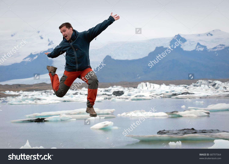 Young Tourist Jumping, Jokulsarlon Glacier Lake In Background.