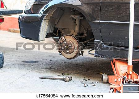 Stock Photo of Jacking up a car with the emergency jack k17564084.