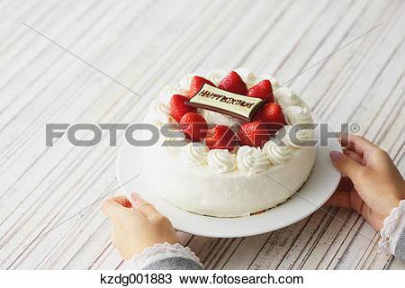 Stock Photo of Young Japanese girl holding strawberry cake.
