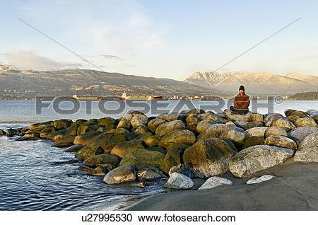 Stock Photography of Man meditating on rocks in Jericho Beach Park.