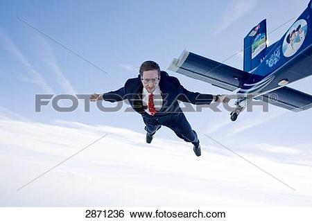 Stock Images of Businessman jumping out of propeller plane.