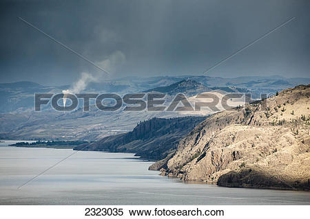 Stock Image of The dry hills of kamloops with a smokestack spewing.