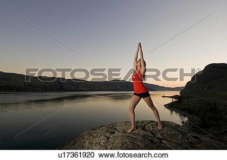 Stock Photography of A young woman practises the art of Yoga over.