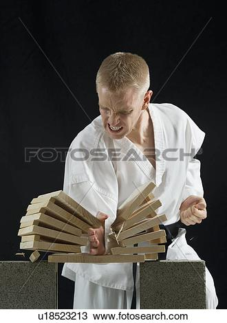 Stock Photo of Young man breaking boards with karate chop on black.