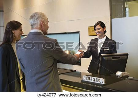 Picture of Business couple getting key card at the hotel reception.