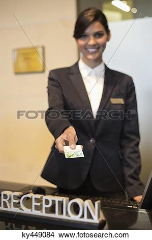 Stock Photo of Receptionist holding a key card and smiling at the.