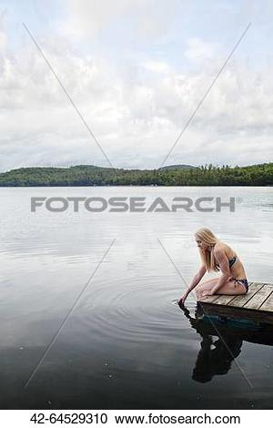 Stock Photography of Woman resting on pier, Kezar Lake, Maine, USA.