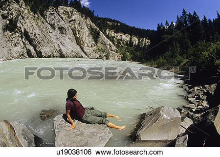 Stock Images of young woman relaxing along the kicking horse river.