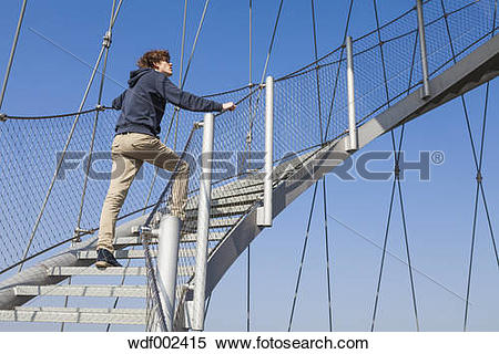 Stock Image of Germany, Stuttgart, Teenage boy climbing stairs of.