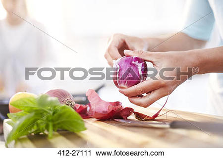 Stock Photography of Woman peeling red onion in kitchen 412.