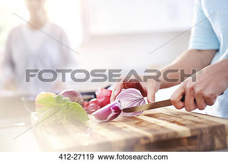 Stock Photograph of Woman slicing red onion on cutting board in.