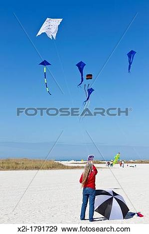 Stock Photograph of Woman flying kite with a Dali style clock face.