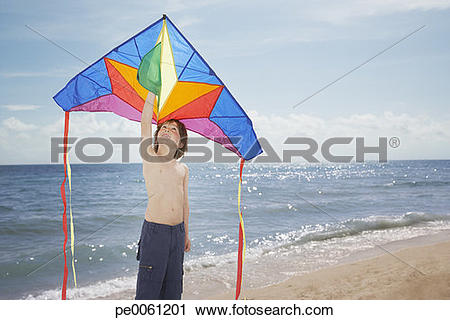 Stock Photography of Young boy at the beach holding a kite.