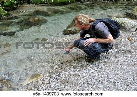 Stock Photo of A male hiker takes a break to fill his water bottle.