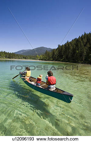 Stock Photo of Young family canoeing on Loon Lake in the East.