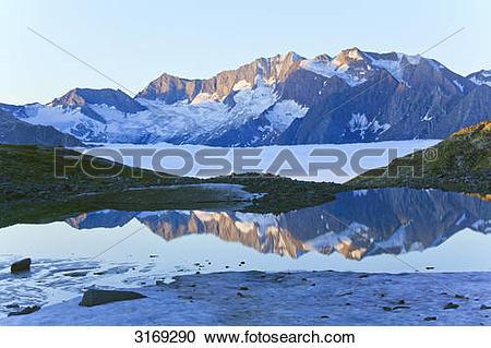 Stock Photography of Mountain lake reflecting Zillertal Alps.