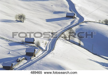 Stock Image of High angle view of log cabins on snowcovered.