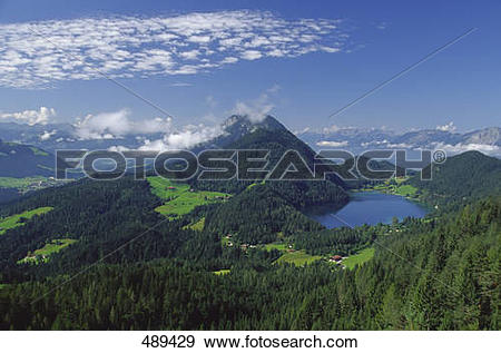 Stock Photograph of Aerial view of lake surrounded by mountain.
