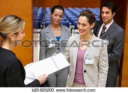 Stock Photography of Hostess supplying documentation to.