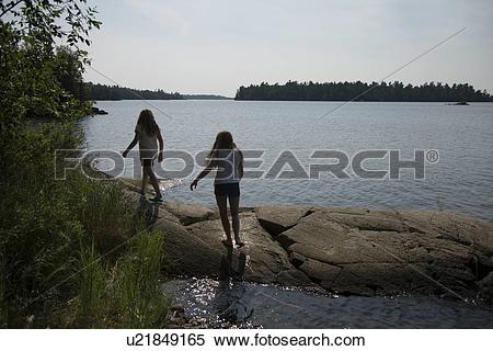 Stock Image of Girls walking on the rocks at the lakeside, Lake of.
