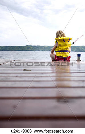 Stock Photo of Young girl wearing life preserver fishing off the.