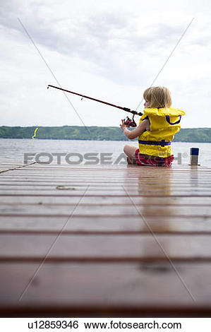 Stock Images of Young girl wearing life preserver fishing off the.