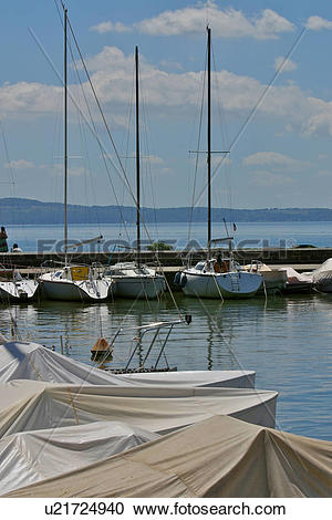 Stock Photography of Yachts in harbour, with jetty beyond, blue.