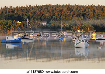Stock Photography of Pleasure boats and fishing boats in mist at.