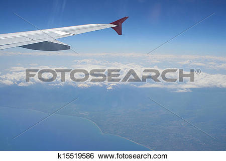 Stock Images of View of jet plane wing with land and sea below.
