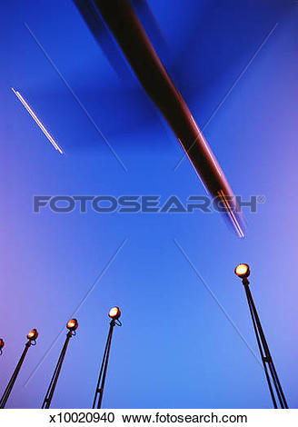 Stock Photography of Aeroplanes coming into land over spotlights.
