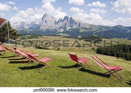Stock Image of Italy, South Tyrrol, Deck chairs on alpine meadow.