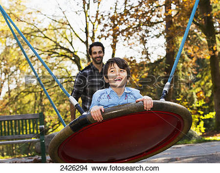 Stock Photo of Father and son having fun together at a playground.