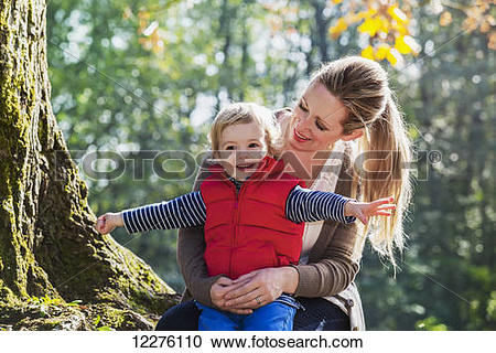 Stock Photography of A mother holding her toddler son in a park in.