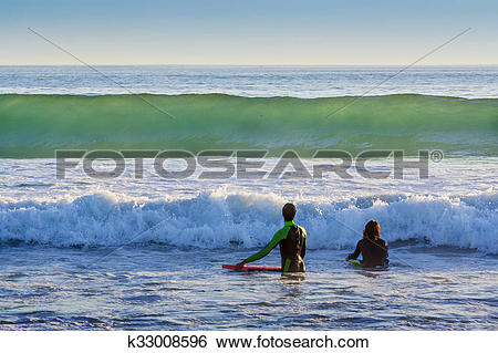 Stock Images of Two surfers against the wave k33008596.