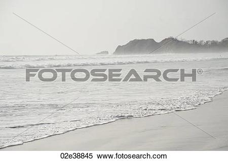Stock Image of Overcast day at the seaside with waves lapping up.