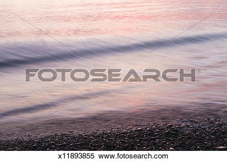 Stock Image of Water reflecting sunset colors, lapping seashore.