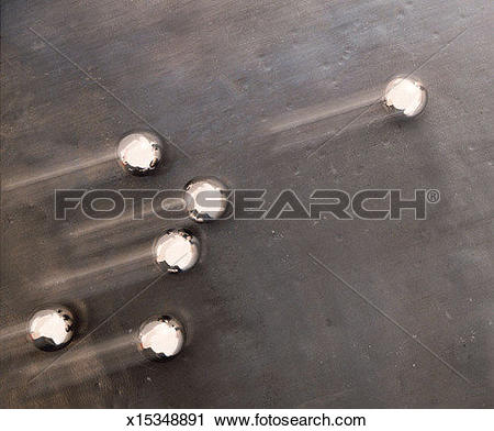 Stock Photography of time lapsed steel balls roll along a cement.
