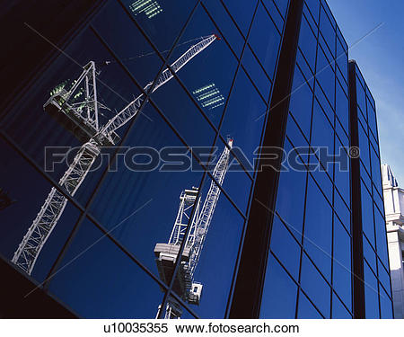 Stock Image of Lattice boom cranes reflected in modern glass.