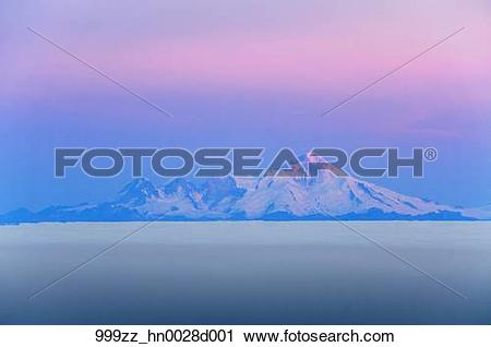 Stock Photography of Daybreak on Mt. Iliamna and a low cloud layer.