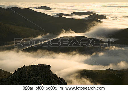 Stock Photo of Hiker on Rock Views Cloud Layer Caribou Pass AK.