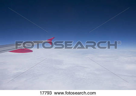 Stock Photo of Airplane wing over layer of clouds and blue sky.