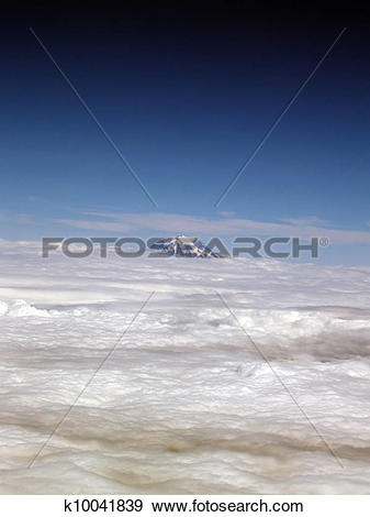 Stock Photograph of Single Mountain Top Amid Layer of Clouds.
