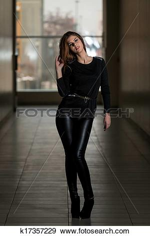 Stock Photograph of Fashion Girl Wearing Leather Pants And Long.