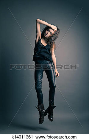 Stock Photography of Fashion model wearing leather pants jump on.