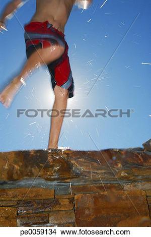 Stock Photo of Boy's legs kicking water on stone wall pe0059134.