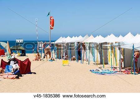 Stock Images of Green flag beach with beach tents, Praia da Nazare.