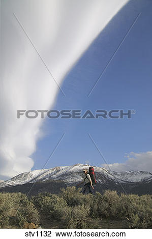 Stock Photo of A woman hiking beneath a lenticular cloud near.