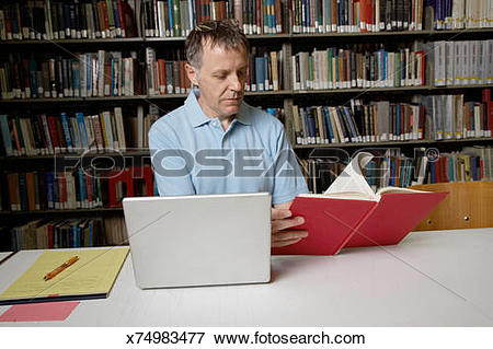 Picture of Mature man sitting at library table with laptop.
