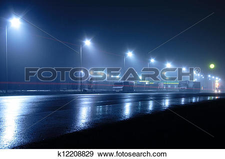 Stock Photograph of lights and light traces on road in the fog.