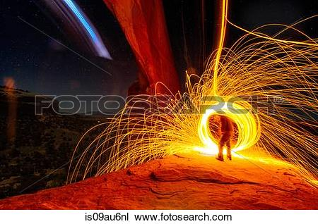 Stock Photo of Mature man creating long exposure light painting on.